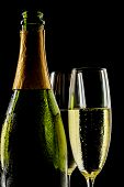 foto of flute  - Champagne bottle and flutes isolated on a black background - JPG