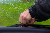 picture of wiper  - the man in the rain repairs a window wiper by car - JPG
