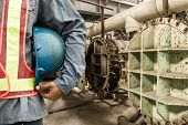 picture of millwright  - construction worker checking location site with crane on the background - JPG