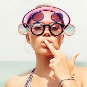 stock photo of middle finger  - Young blonde girl in sunglasses showing middle finger - JPG