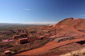 foto of iron ore  - Iron ore mining operations near Tom Price in the Pilbara region of Western Australia under a blue sky with dark red ore rich soils - JPG