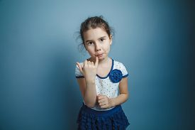 picture of finger-licking  - a girl of seven European appearance brunette licks a finger on a gray background - JPG
