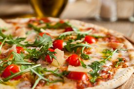 """image of black-cherry  - Italian pizza """"Caprese"""" lies on beautiful wooden table. At the top of a pizza cut baked cherry tomatoes arugula and Parmesan cheese slices. Nearby are the containers with spices and olive oil. ** Note: Shallow depth of field - JPG"""