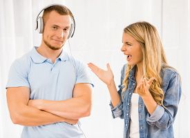 foto of ignore  - Wife shouting on her husband while he standing with headphones and ignoring her - JPG