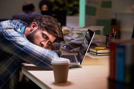 picture of late 20s  - Male Office Worker Asleep At Desk Working Late On Laptop - JPG