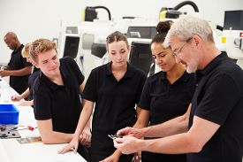 pic of micrometer  - Engineer In Factory With Apprentices Checking Components - JPG