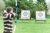 An archer with bow takes aim at a target during competition