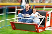 stock photo of amusement park rides  - Faces of excitement from a father and daughter as they enjoy the fast octopus ride in the park - JPG