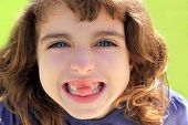 indented little girl sticking tongue between teeth smiling portrait