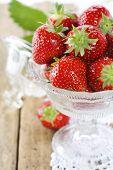 Cristal antiguo lleno de fresas frescas sabrosos y encaje vintage