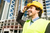 Civil engineer or architect checks progress of construction works at building site of high-riser poster