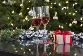 two red drinks and small christmas present by tree with lights, bows