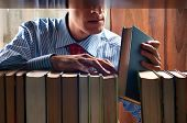 stock photo of book-shelf  - men put a book on to the bookshelf - JPG