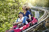 Smiling women and her boy riding downhill together on an outdoor roller coaster on a warm summer day poster