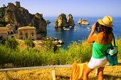 Attractive girl taking photograph of beautiful european coastal scene