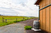 stock photo of water shortage  - Gutters direct rainwater into a wooden rain barrel on the side of a building - JPG