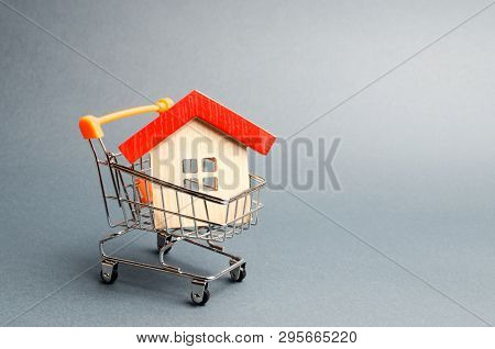 poster of Wooden House In A Supermarket Trolley. The Concept Of Buying A House Or Apartment. Affordable Housin