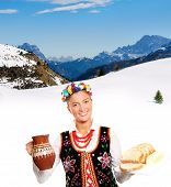 A portrait of a beautiful and hospitable Polish woman in a traditional outfit over mountain backgrou