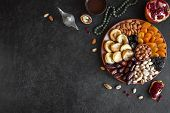 Traditional Muslim Iftar Food On Black, Copy Space. Ramadan Kareem With Dates, Nuts, Dried Fruits An poster