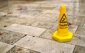 Yellow Cone With Caution Slippery Surface Sign, On Wet Pavement Tiles. poster