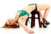 stock photo of bending over backwards  - Young women in bikini bending backwards over stool against white background red hair and high heals - JPG