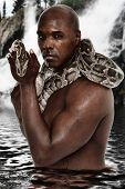 Attractive Fit Black Man with Boa Constrictor Standing in Lake in front of Waterfall