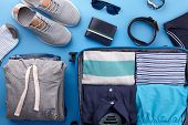 Packing Mens Summer Clothes And Accessories In Blue Travel Suitcase On Blue Background, Top View poster