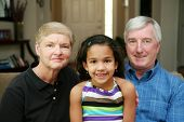 pic of mixed race  - Senior couple together in their home with their granddaughter - JPG
