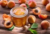 Apricot jam and ripe apricots on the wooden table. poster