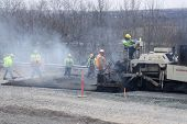 Trabalhadores pavimentando A estrada