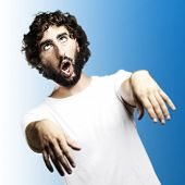 young man imitating a zombie against a blue background