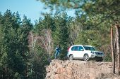 Young Stylish Woman On Cliff With White Suv Car. Travel Concept poster