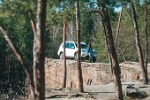White Suv Car At Rocky Cliff Young Woman Near It. View Through Trees poster