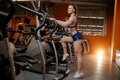 Athletic Young Woman Ready For Exercise On Cardio Machine In The Gym. poster