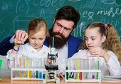 Man Bearded Teacher Work With Microscope And Test Tubes In Biology Classroom. How To Interest Childr poster