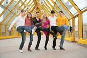 stock photo of team building  - group of young people dance cancanon footbridge - JPG