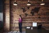 Businesswoman Standing Chatting On Her Mobile Phone In A Large Spacious Office Below A Decorative Ma poster