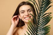 Close Up Brunette Half Naked Woman 20s With Perfect Skin, Nude Make Up Palm Leaf Isolated On Beige P poster