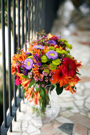 picture of flower vase  - a bouquet of colorful flowers in a vase decorate an outdoor balcony