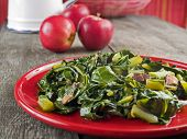 pic of cruciferous  - Collard greens and bacon on a red plate with apples and a water pitcher in the background.