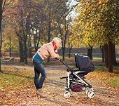 Young mother looking at her child in a baby stroller