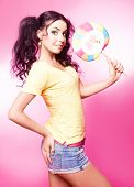pretty young brunette woman with a lollipop, isolated against pink background