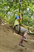 stock photo of parkour  - Preteen girl is coming down at the rope parkour outdoors - JPG