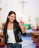 Pretty Young Woman Giving Victory Sign in a church