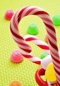 closeup of some candy canes and gumdrops on a woven background