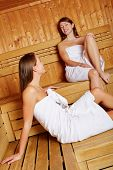Two smiling women relaxing in a sauna and talking