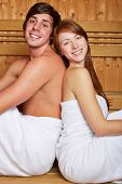 Young happy couple sitting in a mixed sauna