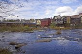 picture of water-mill  - Ammonoosuc River flowing across rocks and under a covered bridge in Littleton New Hampshire - JPG