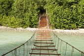 stock photo of daring  - A Rusty Dangerous Bridge Leads over a Turquois River into the Woods - JPG