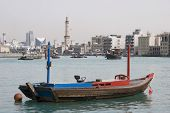 Dubai UAE empty abra anchored on Dubai Creek with minaret of Grand Mosque in distance